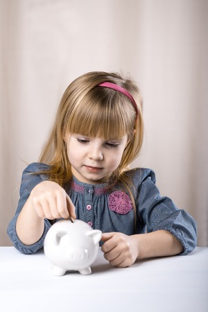 economizing: Child putting coin into piggy bank.