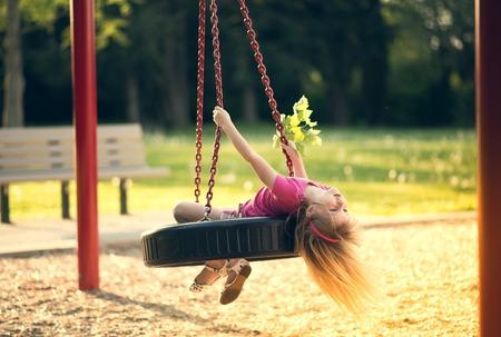 niños en area de juegos: Niña que hace pivotar en el oscilación en el parque.