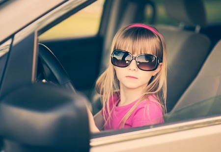 Little girl in sunglasses driving a car.