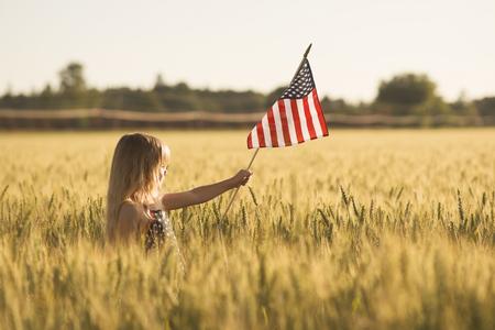 julio: Niña con la bandera de Estados Unidos Foto de archivo