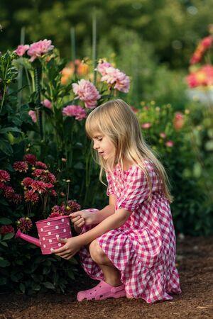 garden flower: Small  girl  watering the flowers