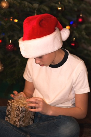 10 12 years: Boy in Santa hat with  Christmas gift. Stock Photo