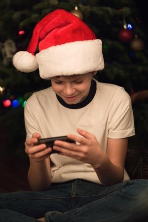 10 12 years: Boy in Santa hat using his smartphone.