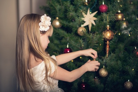 decorating christmas tree: Little girl decorating Christmas tree. Stock Photo