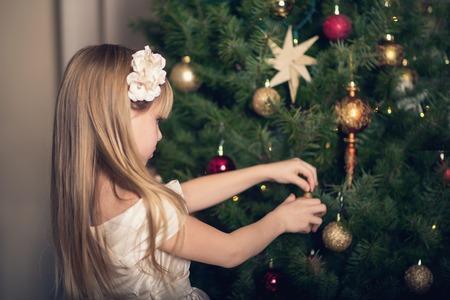 decorating christmas tree: Little girl decorating Christmas tree. Stock Photo