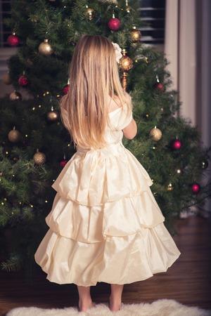 elementary age girl: Little girl decorating Christmas tree. Stock Photo