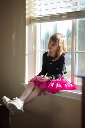 Young Girl in a pink tutu sitting on the window.