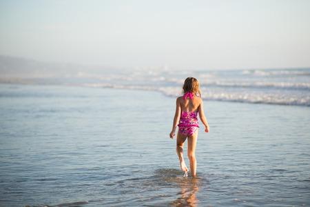 petite fille maillot de bain: Une jeune fille se promène dans les eaux peu profondes dans l'océan.