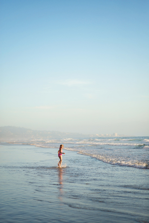 little girl swimsuit: A young girl walks through shallow water in the ocean. Stock Photo