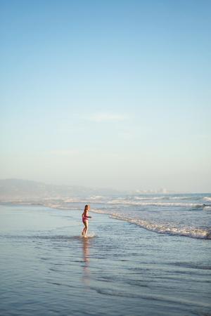 traje de bano: Una ni�a camina a trav�s de aguas poco profundas en el oc�ano. Foto de archivo