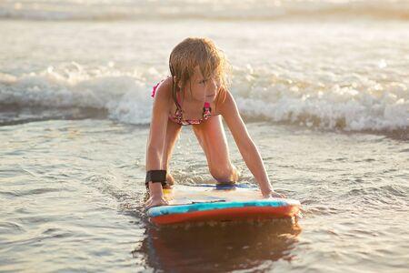 boogie: Little girl riding a boogie board in ocean
