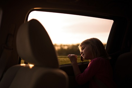 female child: Young girl leaning out a car window at sunset. Stock Photo