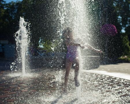 niñas jugando: Niña jugando en una fuente durante el verano