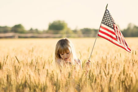 Little girl holding American flag in a field.