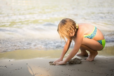 Little girl  plays in the sand at the lakeshore