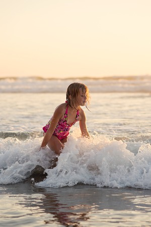 Young girl playing in the waves at sunset