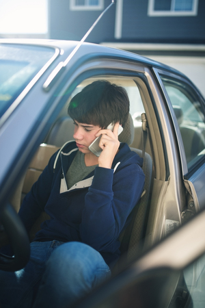 preadolescent: Teen boy using a cell phone in his car.