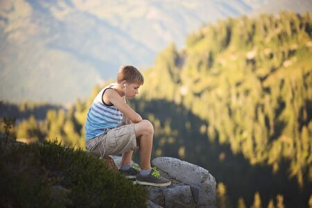 Teen boy sitting on rock at mountain overlook
