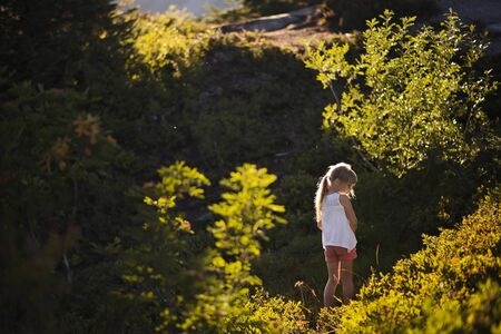 Little girl in forest with streaming sunlight