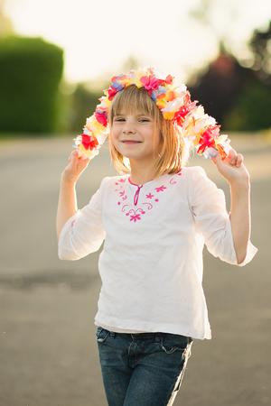 girl holding flower: Portrait of a happy little girl holding flower garland.