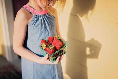 Little girl holding container of strawberries