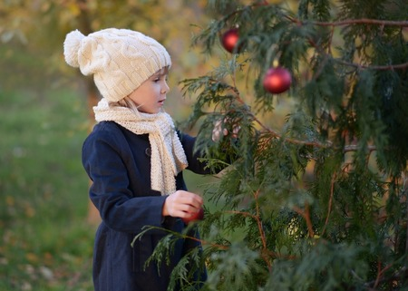 A Young girl decorating a fir-tree outdoor.