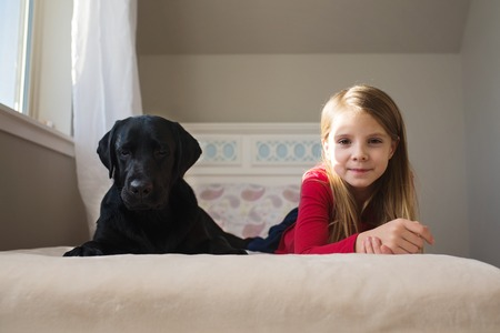 Little girl and her dog on the bed. 版權商用圖片
