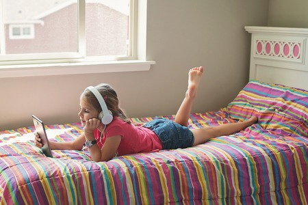 Young girl with headphones and tablet 스톡 콘텐츠