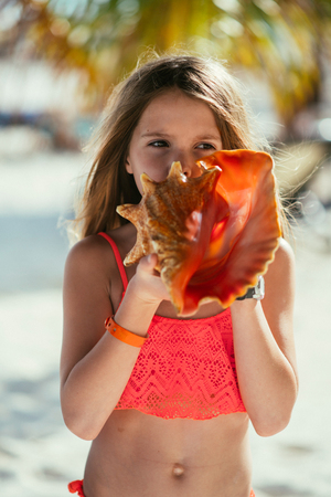 Young girl holding a shell at the beach.