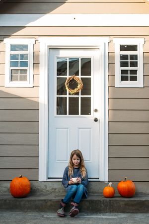 A young girl holding a pumpkin