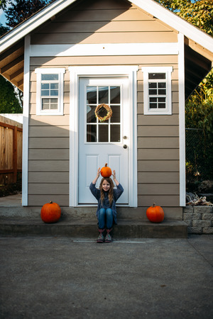 Young girl balances a pumpkin on her head