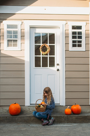 Young girl with basket of pumpkins. 版權商用圖片