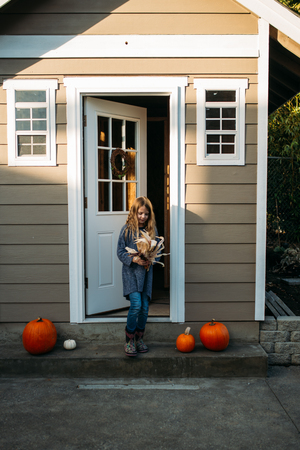 Young girl standing on the porch by the shed.