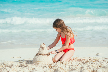 Little Girl making a sand snowman at the  tropical beach 版權商用圖片