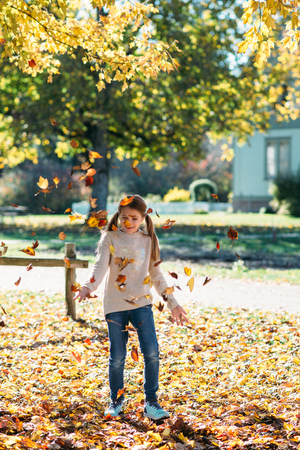Little girl playing outdoors, throwing autumn leaves