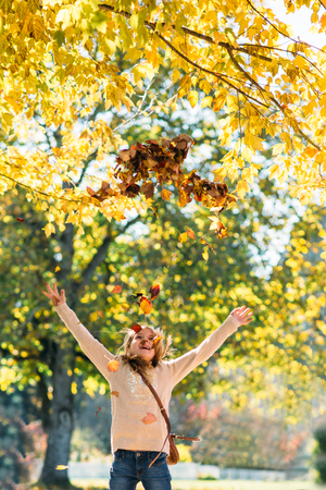 Happy girl throwing autumn leaves in  to the air 版權商用圖片