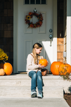 Little girl in front of the  door with pumpkins in the fall 版權商用圖片