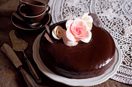 A whole dark chocolate cake with flowers decorations  photo