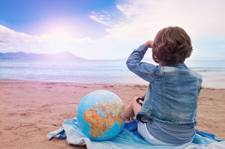 adventure holiday: A Young girl with globe sits on the sand beach and looking at the sunset on sea