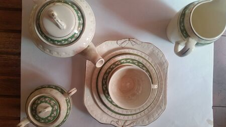 Three porcelain plate, a cup, a teapot, a sugar bowl and a milk jug