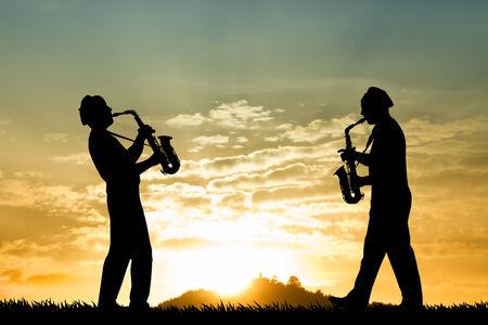 Saxophonists at sunset Stock Photo