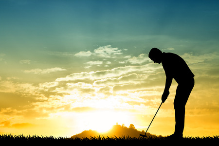 Golfer silhouette at sunset Stock Photo