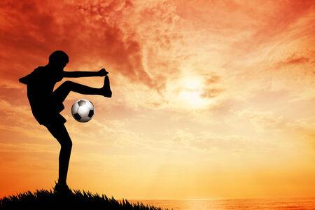 Footballer silhouette at sunset Standard-Bild