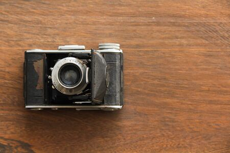 Vintage camera on the wooden background