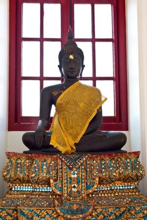 wears: black buddha wears a golden cloth Stock Photo