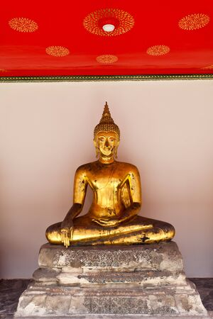 golden buddha sit against the red ceiling photo