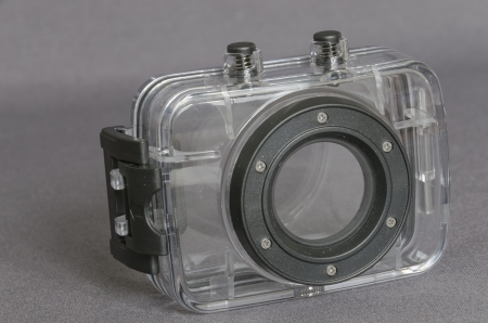staunch: An underwater casing for mini camera sport, on grey bottom  Horizontal, coulour