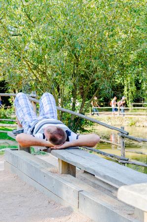 repo: Man sleep on a bench Stock Photo