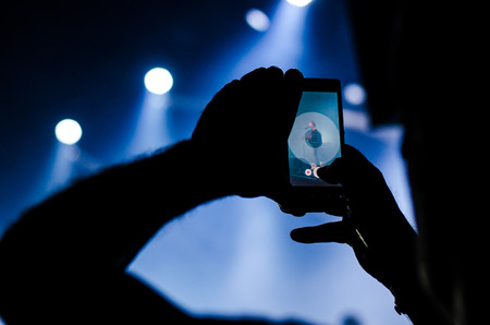 people recording with smartphone at music live show