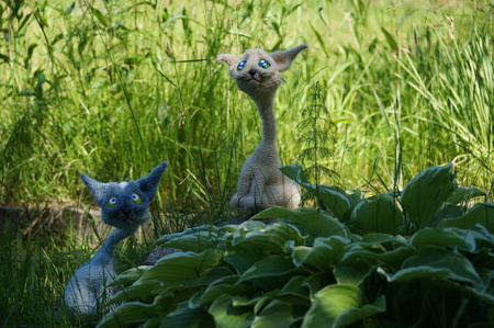 cat gray associated Interior walking toy crochet in the green grass of summer sunny day Stock Photo